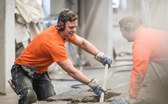Två män i orangea tröjor och med hörselskydd arbetar vid en betongstation med betong. Den ena håller i en pinne och de båda ser glada ut.