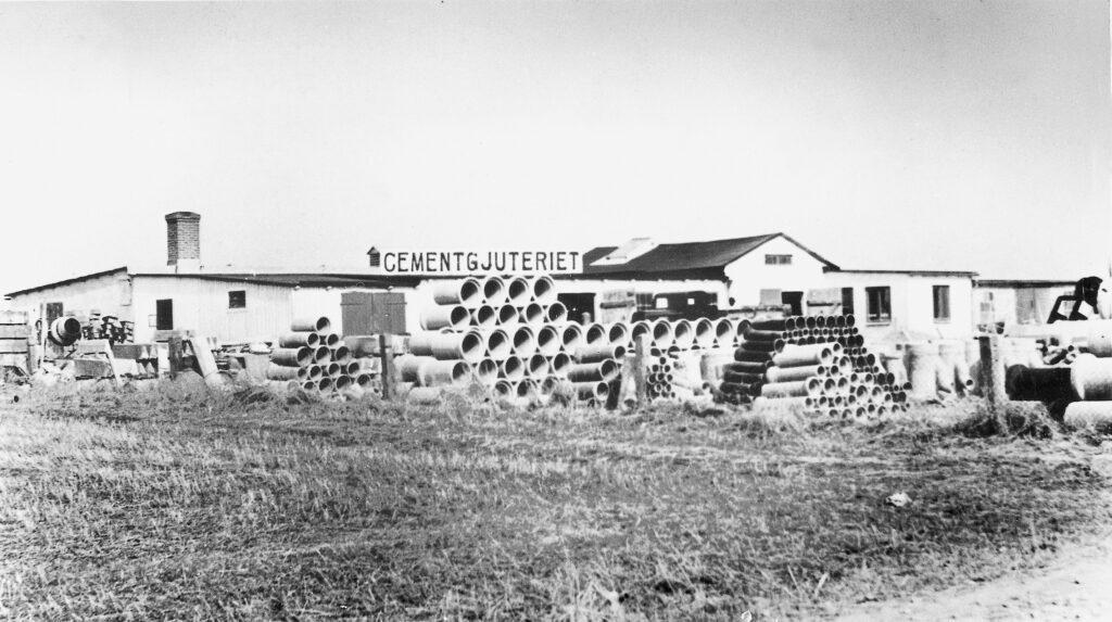 En äldre bild i svartvitt på cementgjuteriet med en text på taket där det står cementgjuteriet med stora bokstäver och där det ligger betongrör travade på marken i förgrunden.